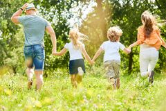 Active family and children run over meadow. Active family and children run across a meadow in summer stock images