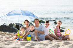 Active family with  children together on beach sitting Royalty Free Stock Photography