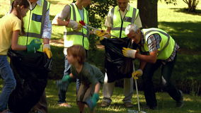 Active family collecting rubbish in park stock video