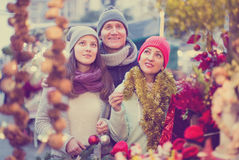 Active family couple with teen girl choosing Christmas decoratio. N at fair Royalty Free Stock Images