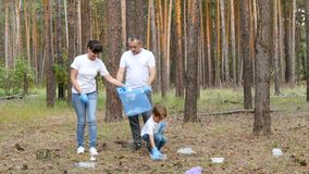Active family: the father, mother and their son clean the Park of debris by putting it in a bag. Education of children`s