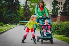 Active family- mother and little girl on roller skates with stroller in city. Active family- happy mother and daughter on roller skates with stroller in city royalty free stock photo