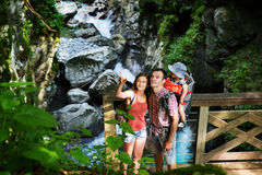 Active family hiking with 1,5 years child in carrier on the back. Ground of a mountain river. Slovenia, Tolmin, Waterfalls of the Kozjak, Tolmin Gorges royalty free stock photo