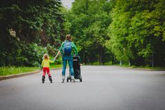 Active family- mother and little girl on roller skates with stroller in city. Active family- mother and daughter on roller skates with stroller in city stock images