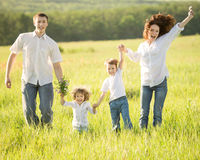 Active family outdoors. Active happy family jumping outdoors in spring green field stock images