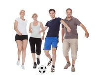Active family playing soccer. Active family with fit parents and two teenagers playing soccer running after a ball isolated on white Royalty Free Stock Image