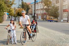 Active family riding bikes in the park summer day. Active life concept royalty free stock photography