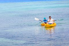 Family at vacation. Active family of two, father and son, enjoying kayaking together, tropical vacation concept, copy space on left Royalty Free Stock Photos
