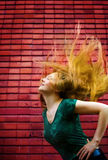 Active fashion woman with hair in motion. Energetic woman with moving hair in front of brick wall Stock Image