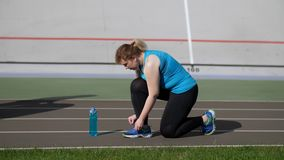 Active fat woman runner tying shoelaces on stadium. Side view of overweight female jogger kneeling on track to tie shoelaces on sneaker during fitness workout on stock video