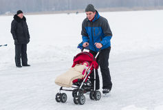 Active father skating with infant in baby carriage on a frozen river Dnepr Royalty Free Stock Photos