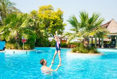 Active father teaching his kid daughter to swim in pool on tropical resort. Summer vacations and sport concept royalty free stock photography