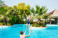 Active father teaching his kid daughter to swim in pool on tropical resort. Summer vacations and sport concept royalty free stock photo