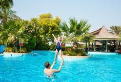 Active father teaching his kid daughter to swim in pool on tropi. Cal resort. Summer vacations and sport concept Stock Photos