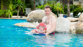 Active father teaching his toddler daughter to swim in pool on tropical resort Stock Image