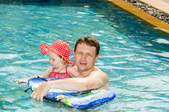 Active father teaching his toddler daughter to swim in pool on tropical resort. Royalty Free Stock Image