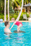Active father teaching his toddler daughter to swim in pool on tropical resort. Royalty Free Stock Photo