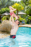 Active father teaching his toddler daughter to swim in pool on tropical resort. Stock Image