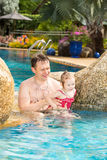 Active father teaching his toddler daughter to swim in pool on tropical resort Stock Photos