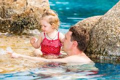 Active father teaching his toddler daughter to swim in pool Stock Images