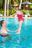 Active father teaching his toddler daughter to swim in pool on tropical resort. Royalty Free Stock Photography
