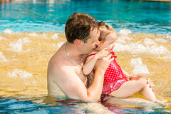 Active father teaching his toddler daughter to swim in pool on tropical resort. Stock Photos