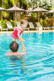 Active father teaching his toddler daughter to swim in pool on tropical resort. Stock Images