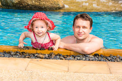 Active father teaching his toddler daughter to swim in pool on tropical resort. Royalty Free Stock Photos