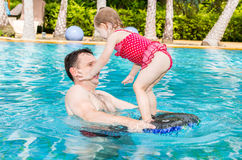 Active father teaching his toddler daughter to swim in pool on tropical resort. Stock Photo