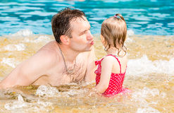 Active father teaching his toddler daughter to swim in pool on tropical resort. Royalty Free Stock Images