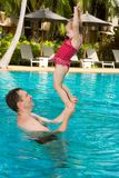 Active father teaching his toddler daughter to swim in pool on  tropical resort in Thailand, Phuket. Royalty Free Stock Photography