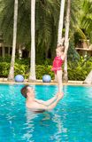 Active father teaching his toddler daughter to swim in pool on  tropical resort in Thailand, Phuket. Stock Photography
