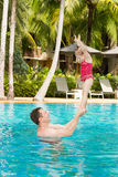 Active father teaching his toddler daughter to swim in pool Stock Image