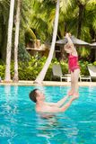 Active father teaching his toddler daughter to swim in pool on  tropical resort in Thailand, Phuket. Royalty Free Stock Photos