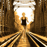 Active female athlete running on railaway tracks. Stock Photography