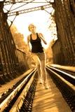 Active female athlete running on railaway tracks. Stock Images