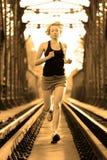 Active female athlete running on railaway tracks. Royalty Free Stock Photo