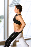Active female in gym club. Beautiful active woman doing her stretching exercise in a modern and spacious interior stock photography
