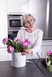 Active female pensioner is preparing flowers for the vase Stock Photo
