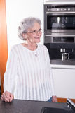 Active female pensioner is standing in the kitchen Royalty Free Stock Image