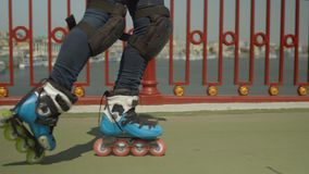 Active female roller feet skating on river bridge. Close-up of skillful woman`s legs in roller skates and knee pads doing cross position riding backwards and stock video