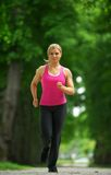 Active female runner in sportswear jogging in the park Stock Images
