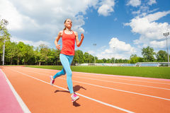 Active female runner working out at stadiums track Stock Photo