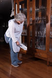 Active female senior is cleaning furniture Royalty Free Stock Photo