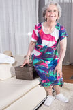 Active female senior is packing vintage suitcase for summer vacation Stock Images
