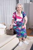 Active female senior is packing vintage suitcase for summer vacation Royalty Free Stock Photo