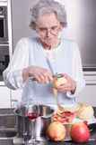 Active female senior peeling apple in the kitchen Stock Images