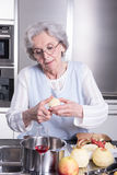 Active female senior peeling apple in the kitchen Royalty Free Stock Photos