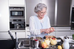 Active female senior peeling apple in the kitchen Royalty Free Stock Photo