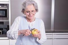 Active female senior peeling apple in the kitchen Stock Photo